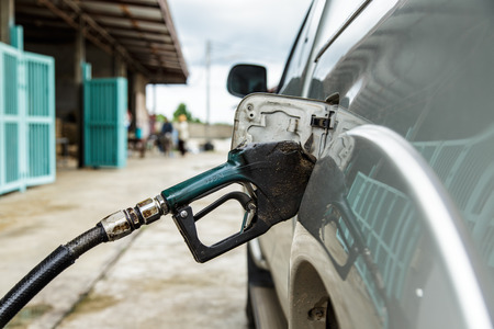 dirty gas pump nozzle in the fuel tank of a pick-up truck photo
