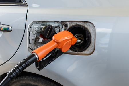 Gas pump nozzle in the fuel tank of a bronze car. photo
