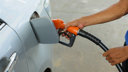 benzine: Closeup of man pumping gasoline fuel in car at gas station.