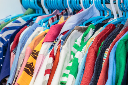 kid clothes of different colors on plastic hanger 스톡 콘텐츠