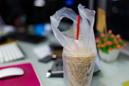 plastic cup: Iced coffee in plastic cup with plastic bag on office table