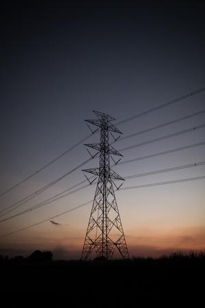 high voltage current: high voltage post at sunset.