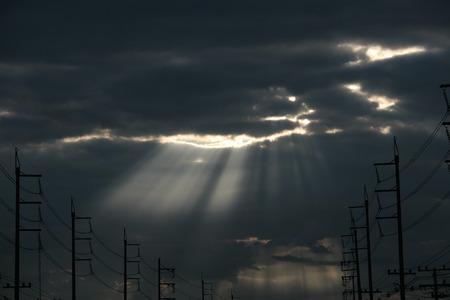 地球を照らしている雲から出てくる太陽光線を背景にシルエット電気ポスト