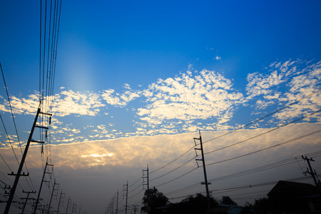 january sunrise: Electricity post silhouetted against a twilit sky. An interesting winter cloud formation, Thailand