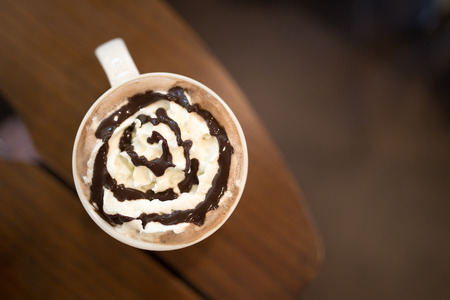Hot chocolate with wipped cream on wooden table, top view