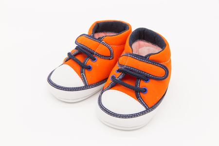 baby shoe: Orange baby shoe isolated on white background Stock Photo