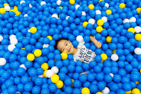 playcentre: A boy in the playing room with many little colored balls. Close portrait