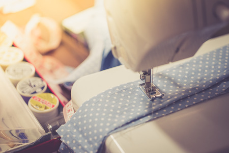 coser: Sewing machine with many sewing utensils on a wooden table, vintage style Foto de archivo