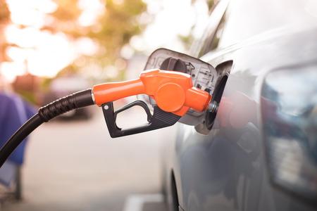 refuel: Gas pump nozzle in the fuel tank of a bronze car, refuel Stock Photo
