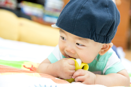 teething: Portrait of sweet baby wearing blue hat. Baby chewing on teething plastic toy