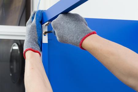 Worker assembling a metal shelf, screwing screw using a manual screwdriver.Do-it-yourself (DIY) concept. 스톡 콘텐츠
