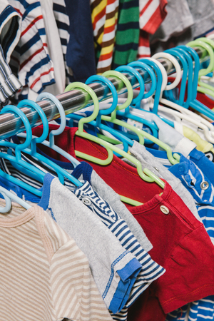 Kid clothes of different colors on plastic hanger 免版税图像 - 49401372