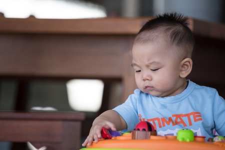 asian ancestry: Little baby boy  playing in the baby walker