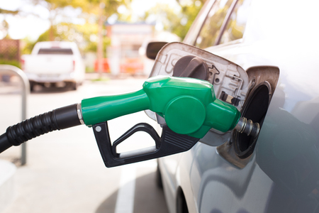 refuel: Gas pump nozzle in the fuel tank of a bronze car. refuel