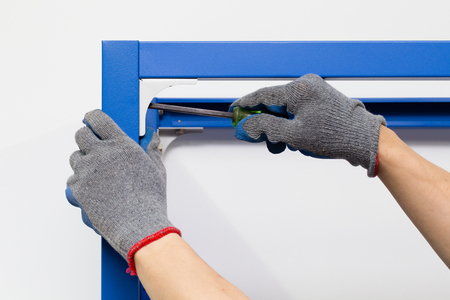 Worker assembling a metal shelf screwing screw using a manual stock photo worker assembling a metal shelf screwing screw using a manual screwdriver it yourself diy concept solutioingenieria Image collections