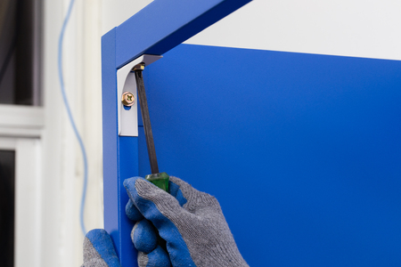 screwing: Worker assembling a metal shelf, screwing screw using a manual screwdriver.Do-it-yourself (DIY) concept. Stock Photo