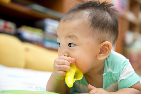 Portrait of sweet baby. Baby chewing on teething plastic toy 免版税图像 - 49401553