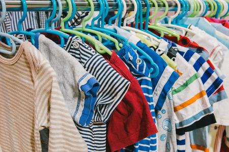 tienda de ropa: ropa del cabrito de diferentes colores en suspensión plástica