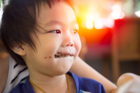 smeared: Smiling kid eating chocolate at coffee shop with his mom. Smeared stained with chocolate lips