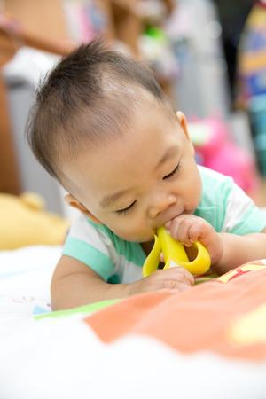 teething: Portrait of sweet baby. Baby chewing on teething plastic toy