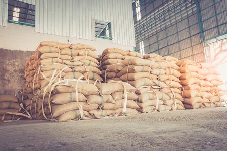 Hemp sacks containing rice in warehouse, vintage style
