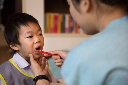 buccal: Mother teaching little boy to brush his teeth