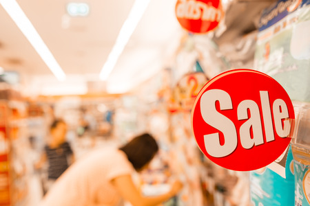 adboard: Red and white sale sign indicating a discount in supermarket, warm retro