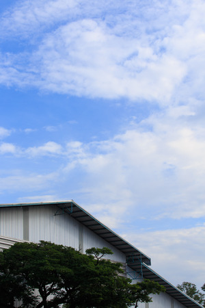 fluffy clouds: White fluffy clouds in blue sky over factory building Stock Photo