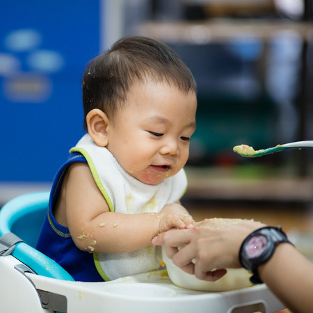 smeared baby: curious and playful baby boy examines and eating baby serial