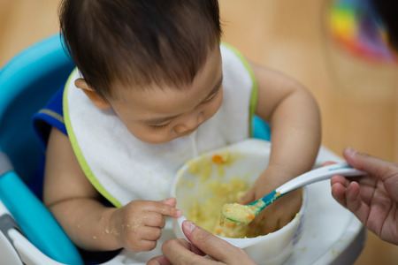 eat smeared baby: curious and playful baby boy examines and eating baby serial