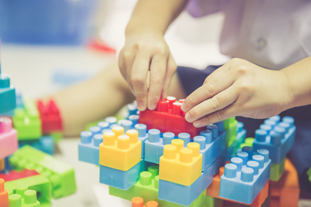 Hand of baby boy playing with colorful blocks, warm retro filter