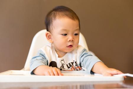 highchair: Happy baby boy in the highchair at restaurant