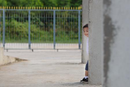 hide and seek: Child playing hide and seek. Cute little boy hiding behind concrete pillar
