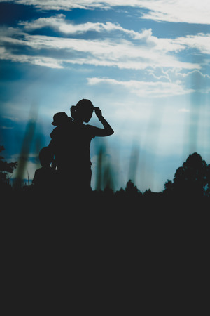 uplift: Mother and 2 little sons silhouettes on field at sunset, cool tone Stock Photo