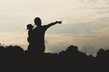 wean: Mother and 2 little sons silhouettes on field at sunset