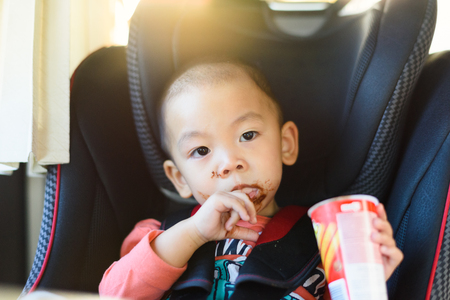 smeared baby: Little boy eating chocolate in safety car seat