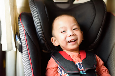 Happy child smiling in safety car seat