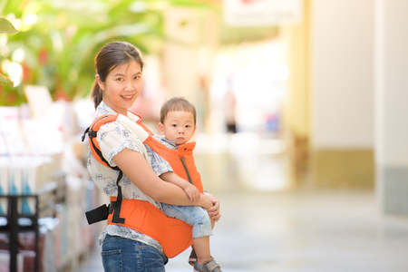 A young asian mother with her baby boy in a baby carrier 免版税图像