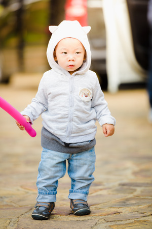 Full-length portrait of adorable little boy wearing jacket with hood. Hands hold twisting balloon.