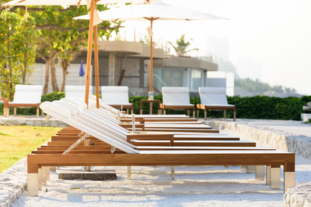 Sun beds and umbrellas at the poolside. 免版税图像