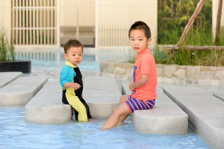 Two happy kids in swimsuit, relaxing in the pool.
