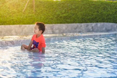 Cute Asian boy playing in swimming pool 免版税图像