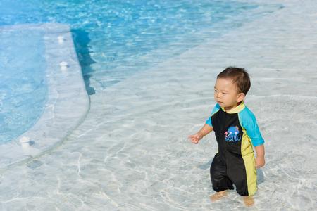 Asian boy wearing swimsuit having fun at the swimming pool