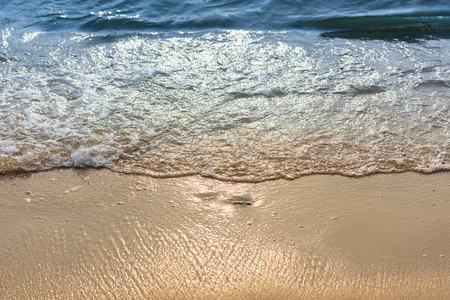 Soft wave of the sea on the sand beach with sunlight. Tropical sandy beach background with copy space. Top down view. 免版税图像