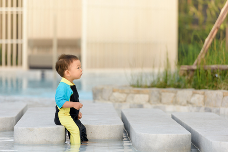 cute baby boy wearing swimsuit in the swimming pool