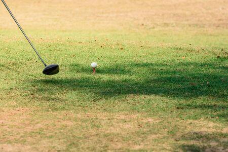 Golf club and ball on a green grass, motion blur