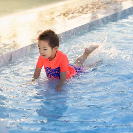 Cute Asian boy playing in swimming pool 스톡 콘텐츠