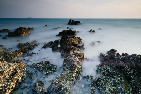 Beautiful rocky sea beach at the sunset 免版税图像 - 131585397