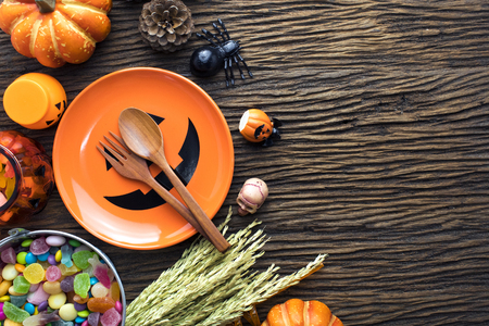 orange dish and decorations of halloween dinner party on wooden table ground