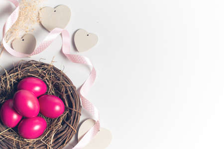 easter eggs pink on background with dried grass with wood vine and flower with ribbon Stock Photo